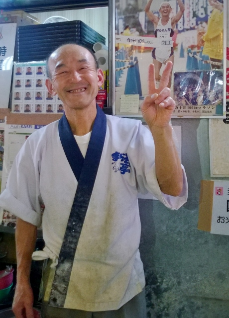 Happy soba master with photo of his marathon exploits behind.