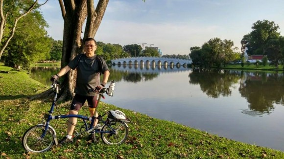 Pastor Richard Wong posing with his Brompton and with Chinese Garden in the background
