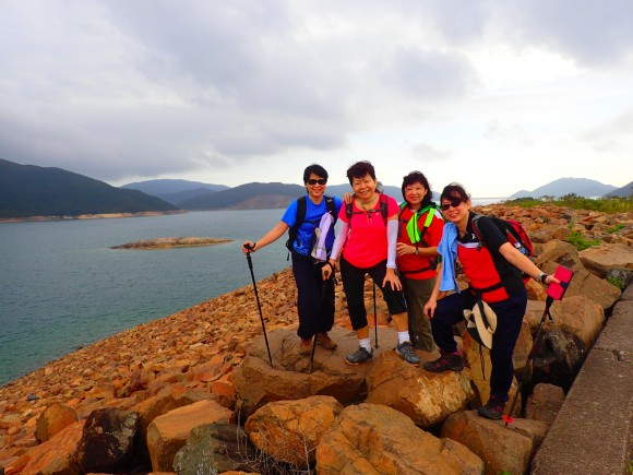 Colourful posing among red reservoir rocks by the shore