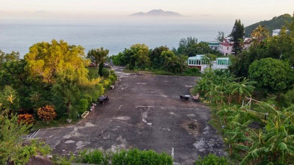 The large tennis court sized yard and sea view.