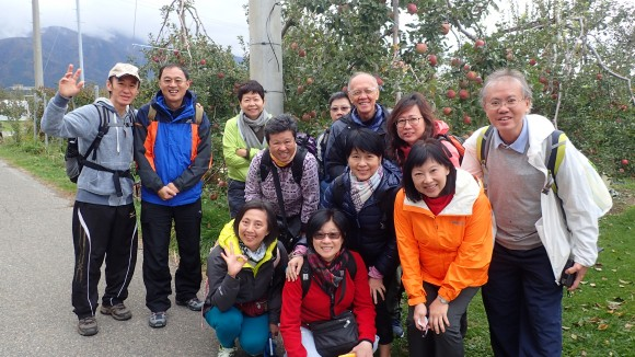 A group photo in front of the apple orchard.