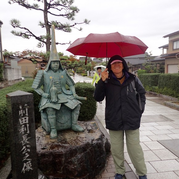 Tan standing beside the statue of